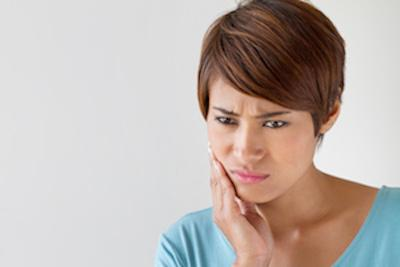 Woman holding jaw from pain | Oakwood Dental