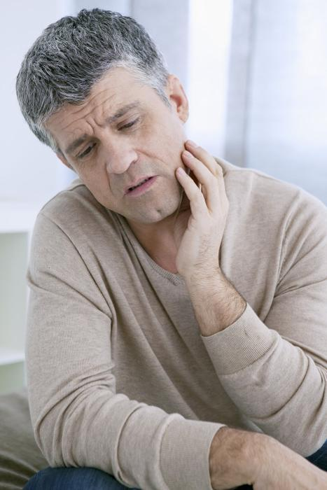 Man holding jaw from TMD pain