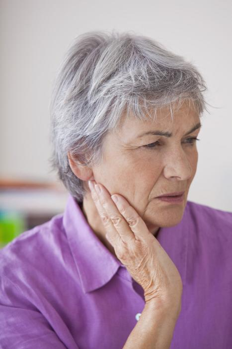 older woman holding jaw from bruxism pain