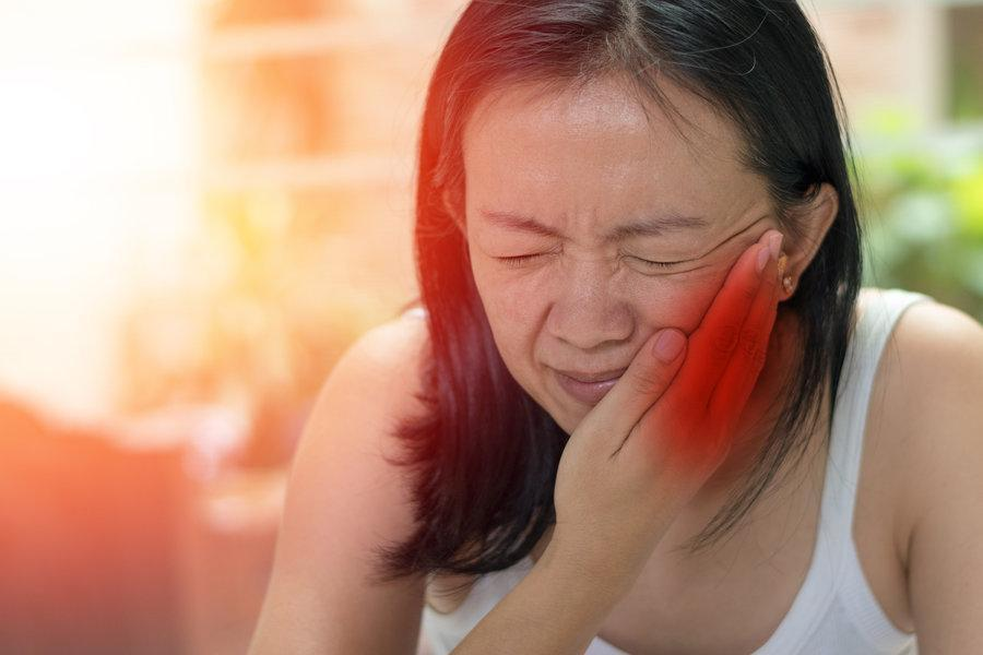 Woman holding jaw from pain | Emergency dentist castle rock co