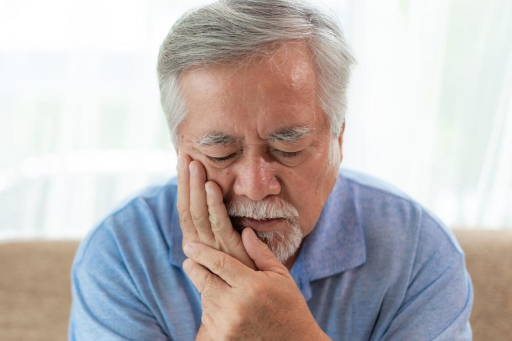 man holding jaw from bruxism pain