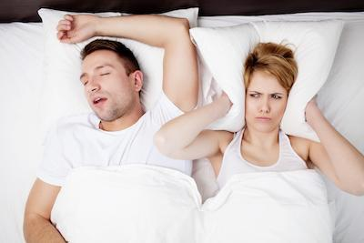 man snoring from sleep apnea and woman covering ears