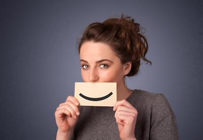 Woman holding up card in front of face with smile | Oakwood Dental
