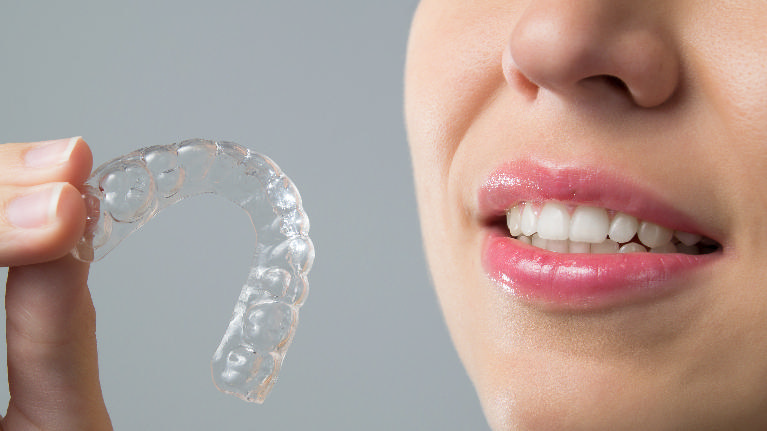 Woman Holding Invisalign Aligner | Dentist Castle Rock CO